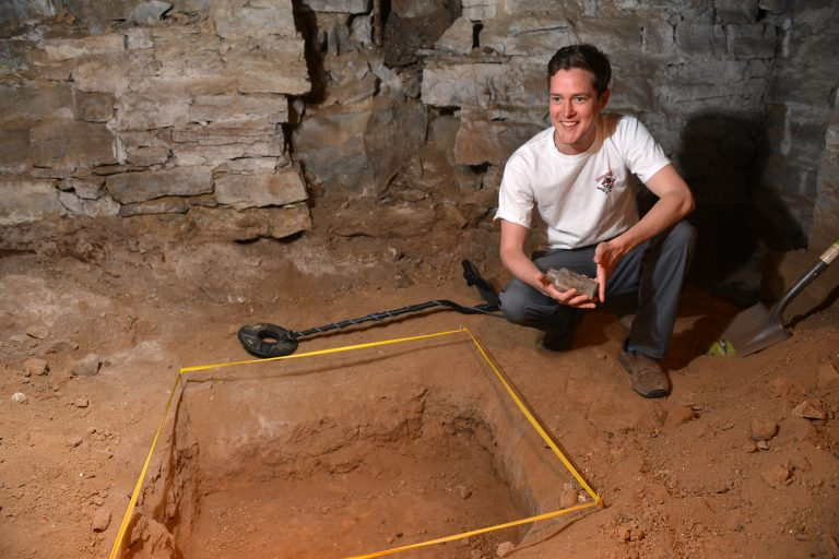 Robert Blythe shows bottle dug on Lotz House Cellar Tour